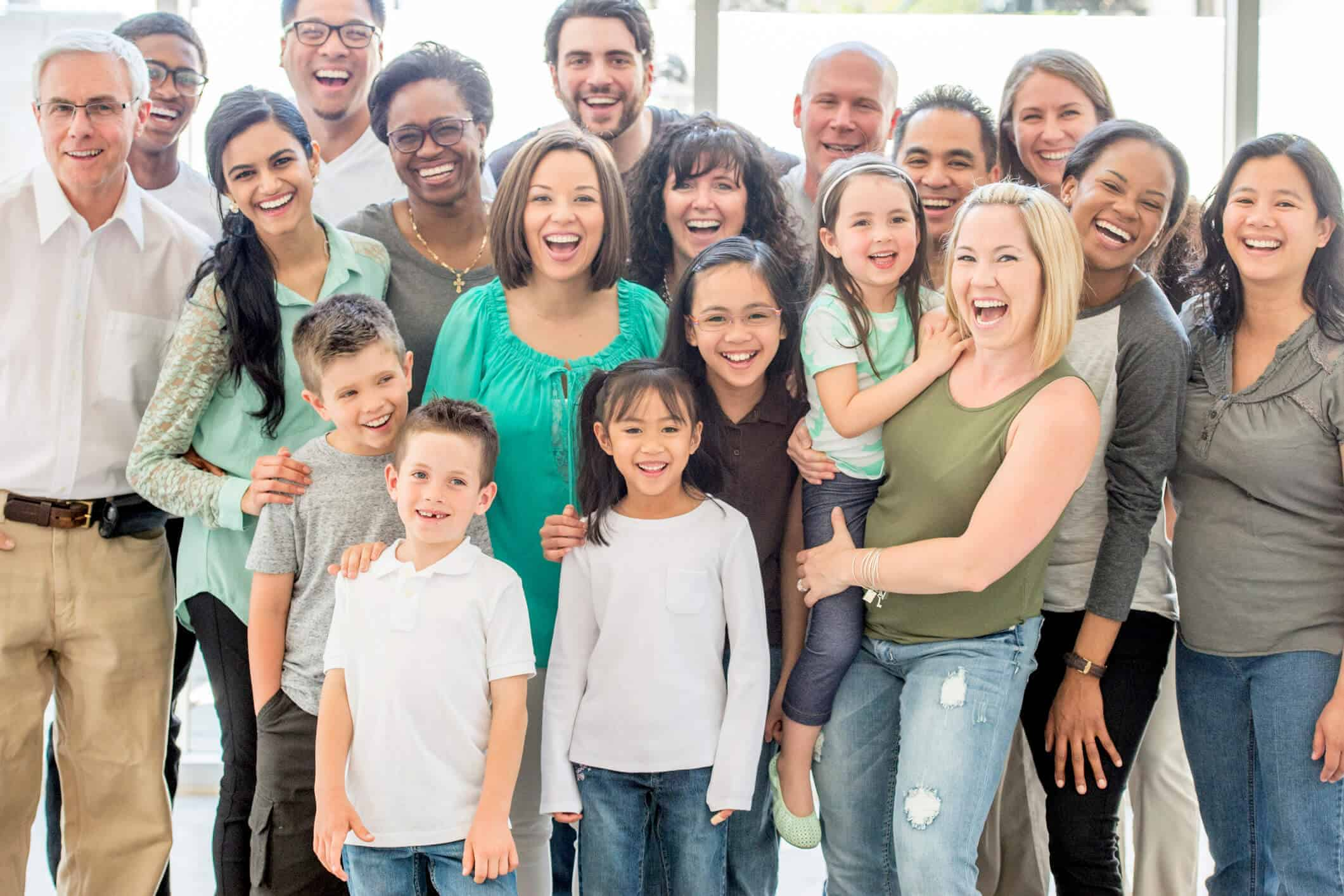 A multi-ethnic and multi-generational group of people standing together, they are smiling and laughing while looking at the camera.