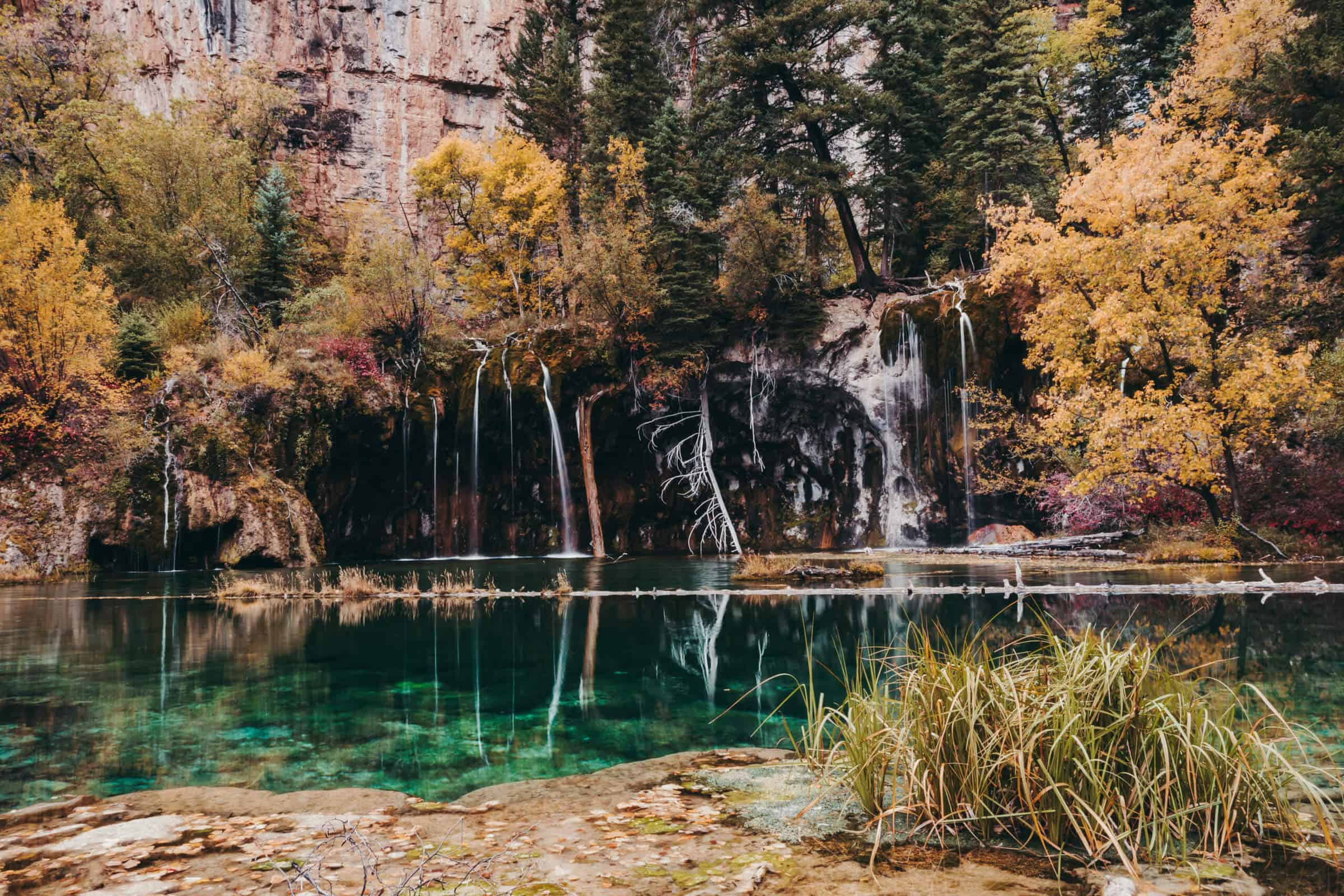 Hanging Lake, alpine lake and waterfalls, near Glenwood Springs, Colorado, during autumn. Lake reflections and fall foliage.